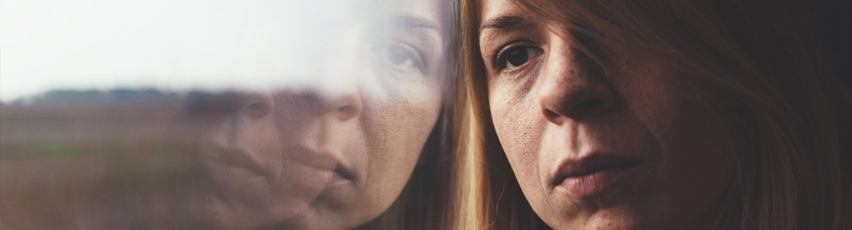 The image is a close up of someone's face. They are leaning against a reflective surface, and the left half of the image is a distorted reflection of their face. While the figure is looking away from the viewer, the distorted reflection faces us. They have long brown hair, freckles and are deep in thought.